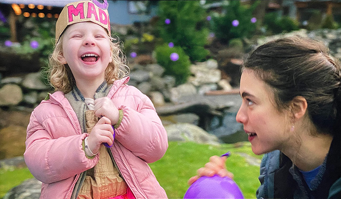 Maid - Rylea Nevaeh Whittet as Maddy laughing, with Margaret Qualley as Alex - photo of Netflix on TV screen